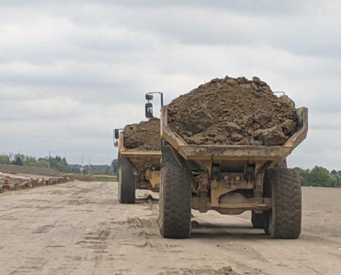 Des camions transportant des matériaux en remblai sur la chaussée nivelée entre les chemins Langstaff et Rutherford